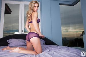 Chloe Miranda poses in purple lingerie on a bed