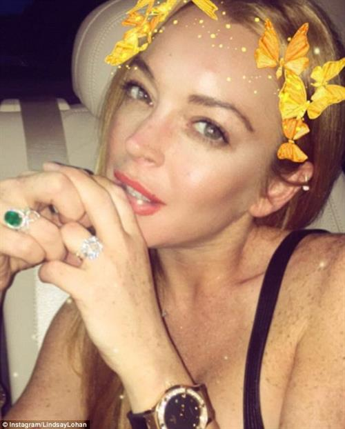A selfie picture of Lindsay Lohan featuring butterflies on her hair along with an emerald engagement ring