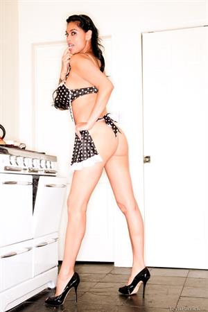 Tera Patrick takes off her black and white apron in the kitchen