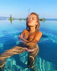 Rita Ora topless boobs new photos on vacation holding her nude big tits wearing a sexy bikini while on vacation.