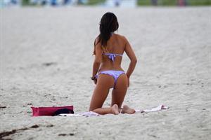 Claudia Romani in a purple thong bikini at the beach
